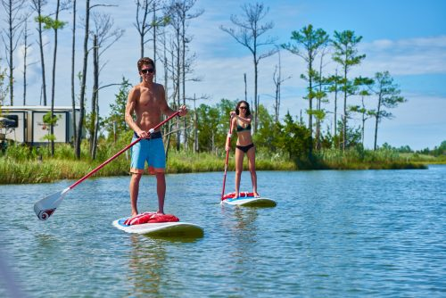 Man and woman in bathing suits atop paddle boards in the water