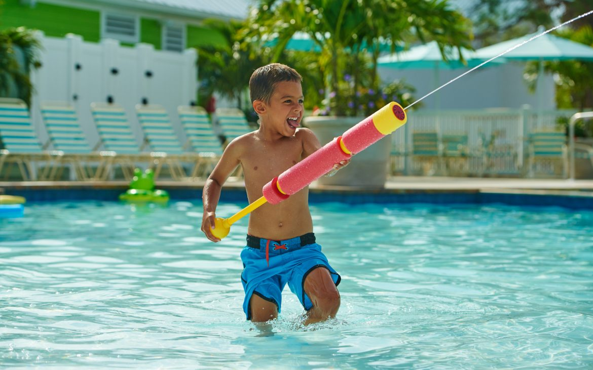 Young child in clear community pool shooting a water gun and laughing