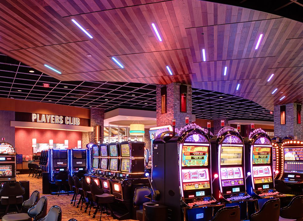 Brightly lit interior of casino with rows of slot machines