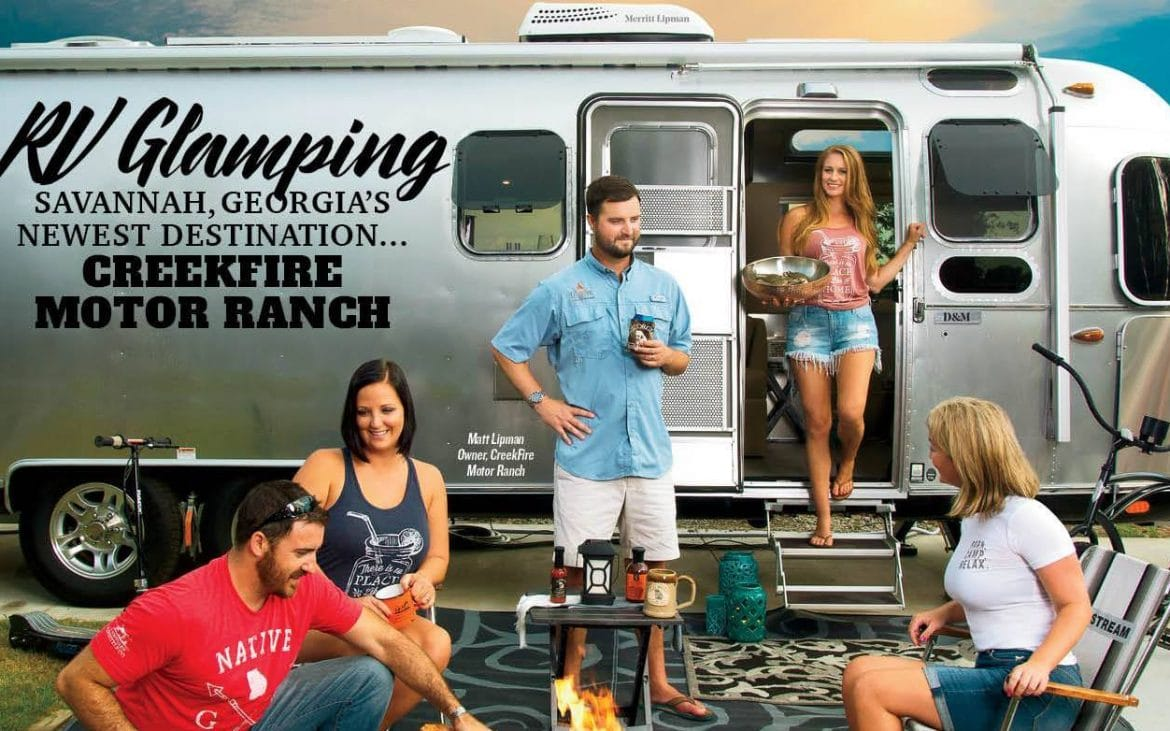 Group of attractive millennials hanging out around campfire infront of trailer