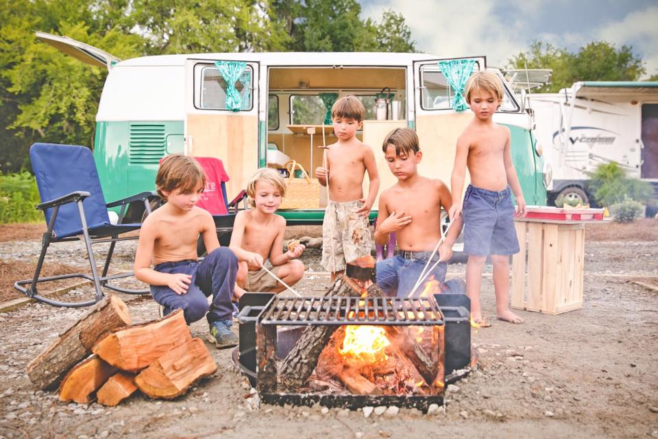 Group of boys hanging out around a campfire in front of VW Bus