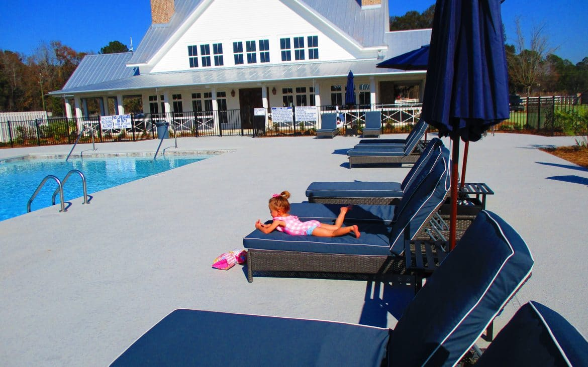 Small girl laying on blue lounger chair beside community pool