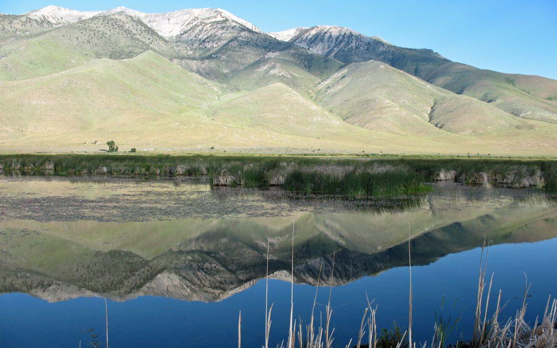 Grassy mountain range reflecting majestically on calm lake
