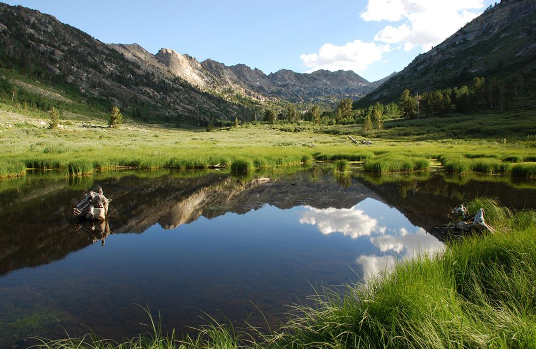 Glassy lake surface reflecting green mountain range and blue sky