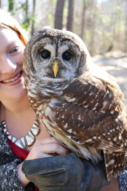 Young woman holding an owl staring at the camera