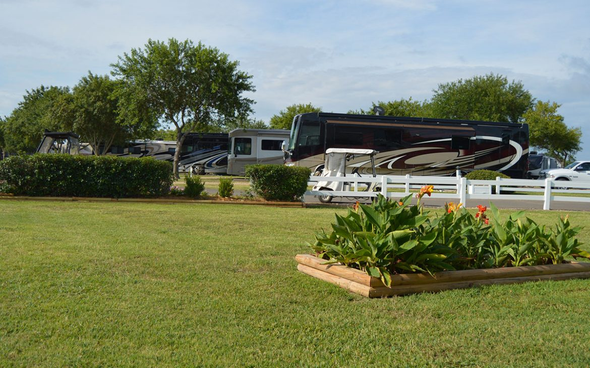 Well groomed lawn and flowers with large RV in background