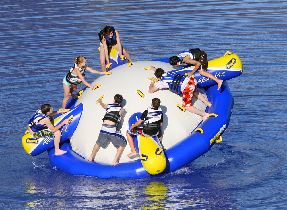 Group of kids playing on large inflatable water toy on lake