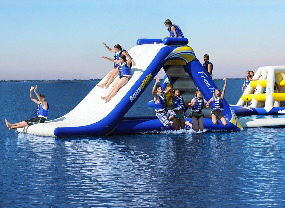 Group of campers playing on inflatable slide floating on a blue lake