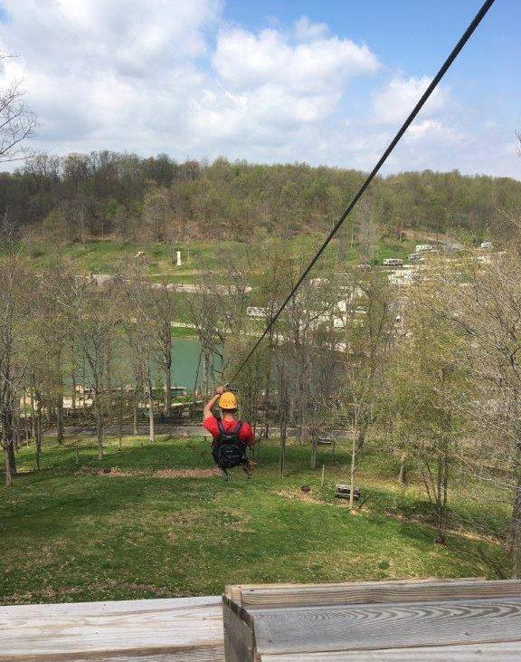 Camper in red jacket and yellow helmet cruising down zipline