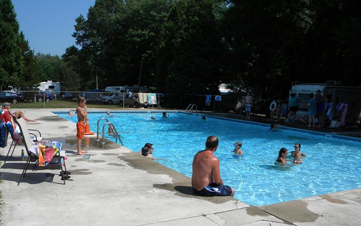Campers swimming playfully in community pool