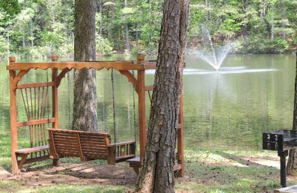 Wooden bench swing overlooking lake surrounded by lush green