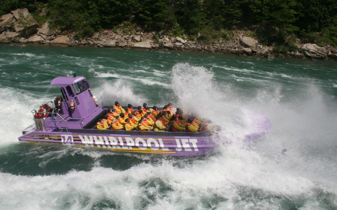 Large purple speedboat with many seats rushing through the water