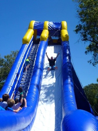 Man sliding down large blue and white inflated slide
