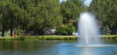 Flowing fountain in the middle of a blue lake with trailers in background