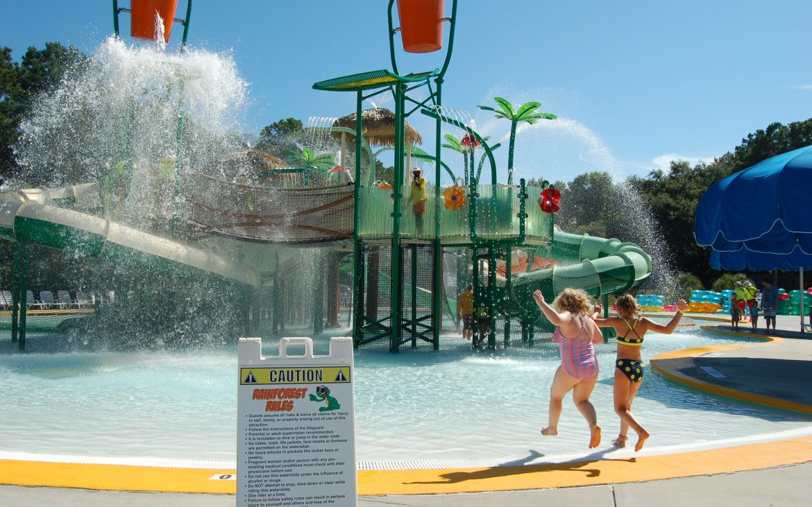 Children playing at colorful waterpark splash pad