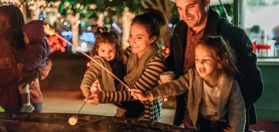 Young family with children roasting marshmallows on a fire.