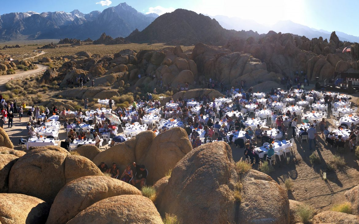 Aerial view of countless people enjoying a concert from tables and tents setup in the rocks