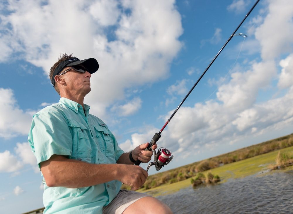 Man in sunglasses and hat fishing under blue skies and clouds