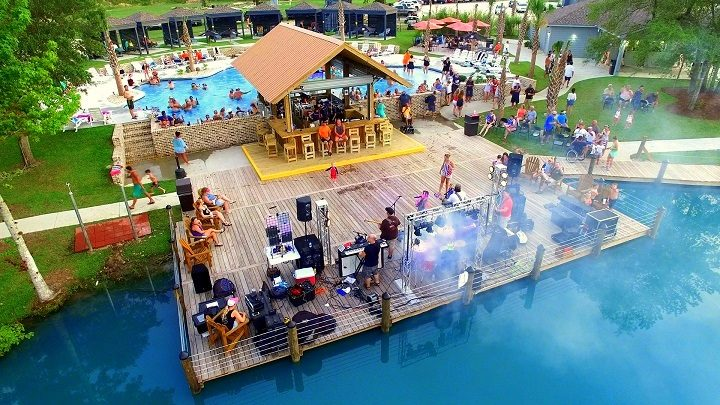 Colorful people performing on dock on pool