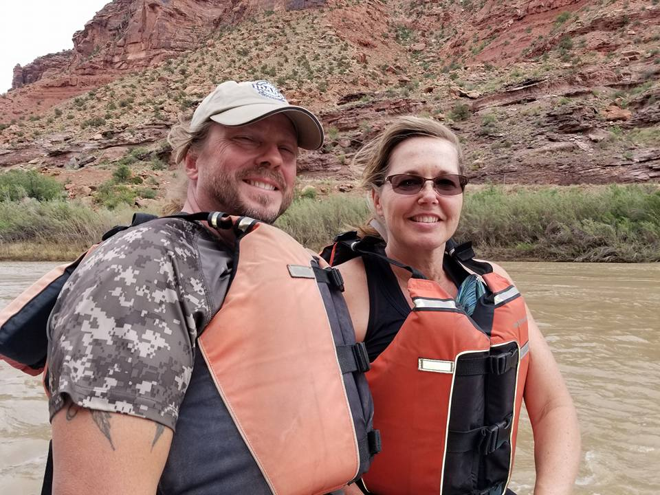 A couple on a Utah riverbank with life jackets.