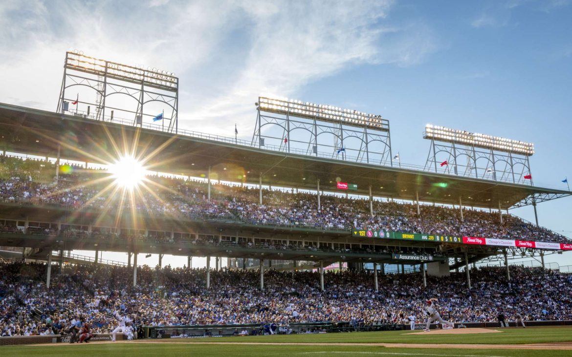 Wide view of Chicago Cubs batter on Wrigley Field with sun in background