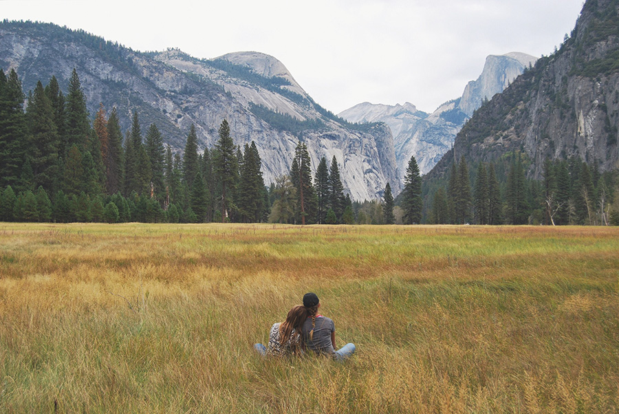 A couple lounges on the grass with Half Dome in the distance.