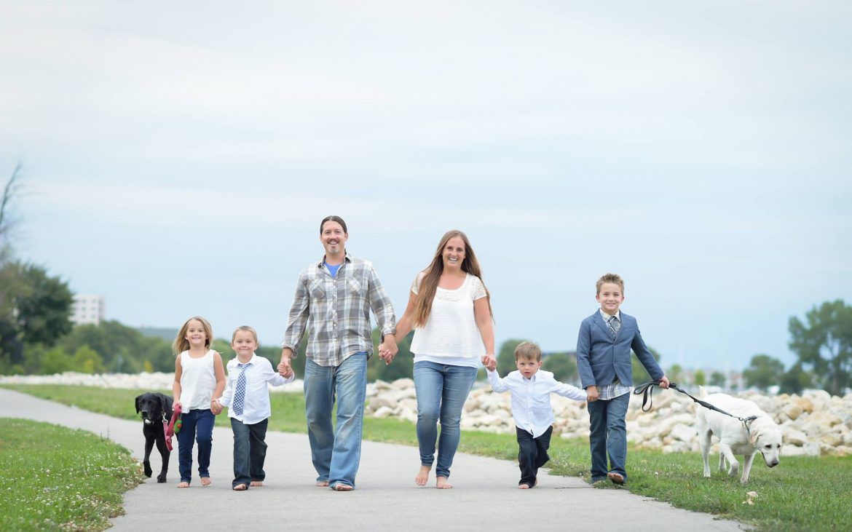 Nice looking family of six walking down road near beach