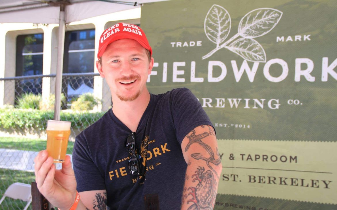 Young man with tattoos smiling holding beer