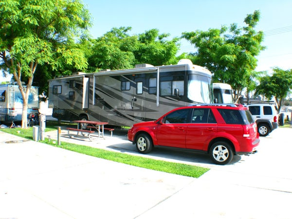 Red Saturn Vue parked in front of large RV