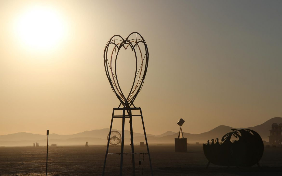 Metal heart sculpture in desert sun