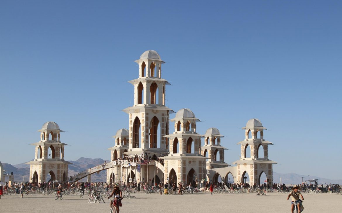 Temple at Burning Man with people on bicycles