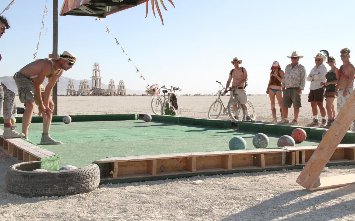 People playing billiards on an outdoor pool table with bowling balls