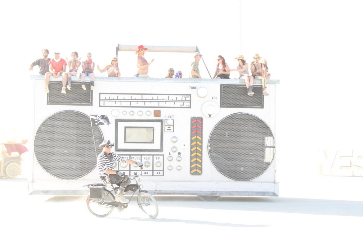 Stereo art car at Burning Man with people on top