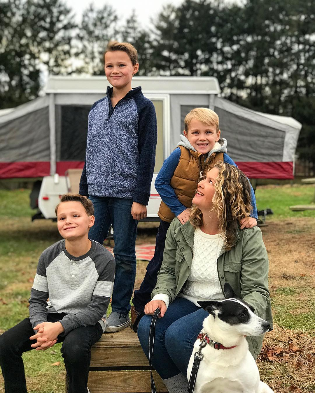 Young woman and mother looking up at three young boys smiling while camping