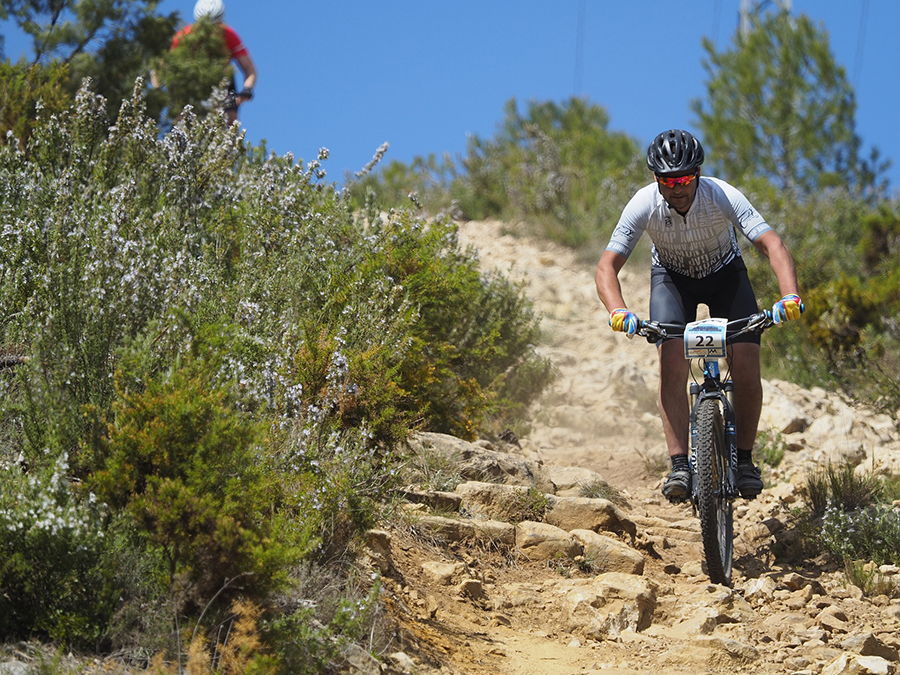 A cyclist rides downhill on a rocky desert trail.