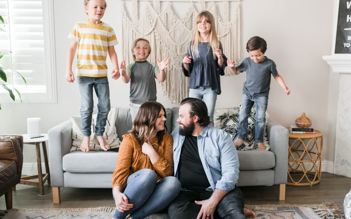 Family of six with four kids standing and jumping on couch