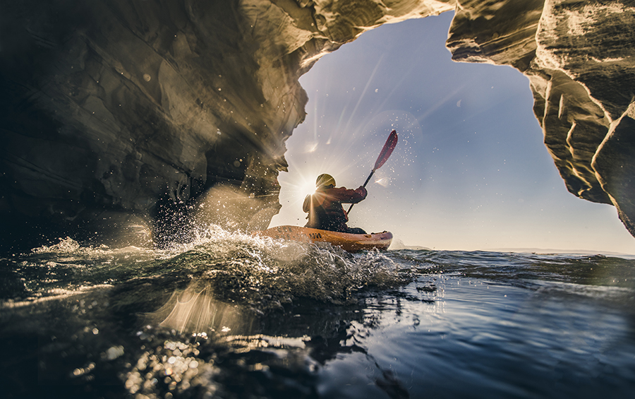 A kayaker exits a cave in the ocean.