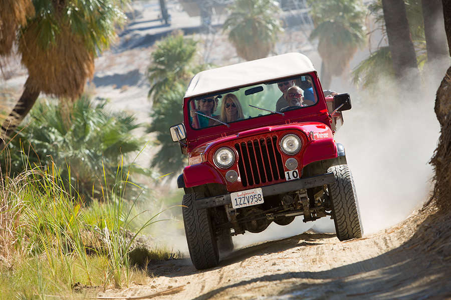 A red jeep churns up dust on a desert trail.