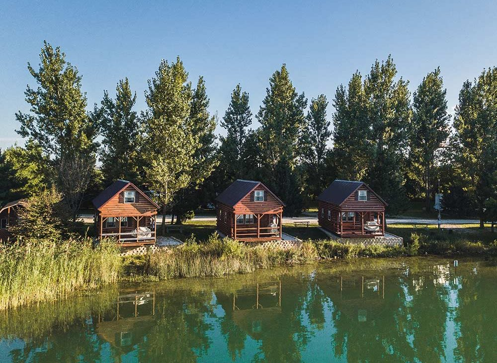 Wooden cabins along tree line and water