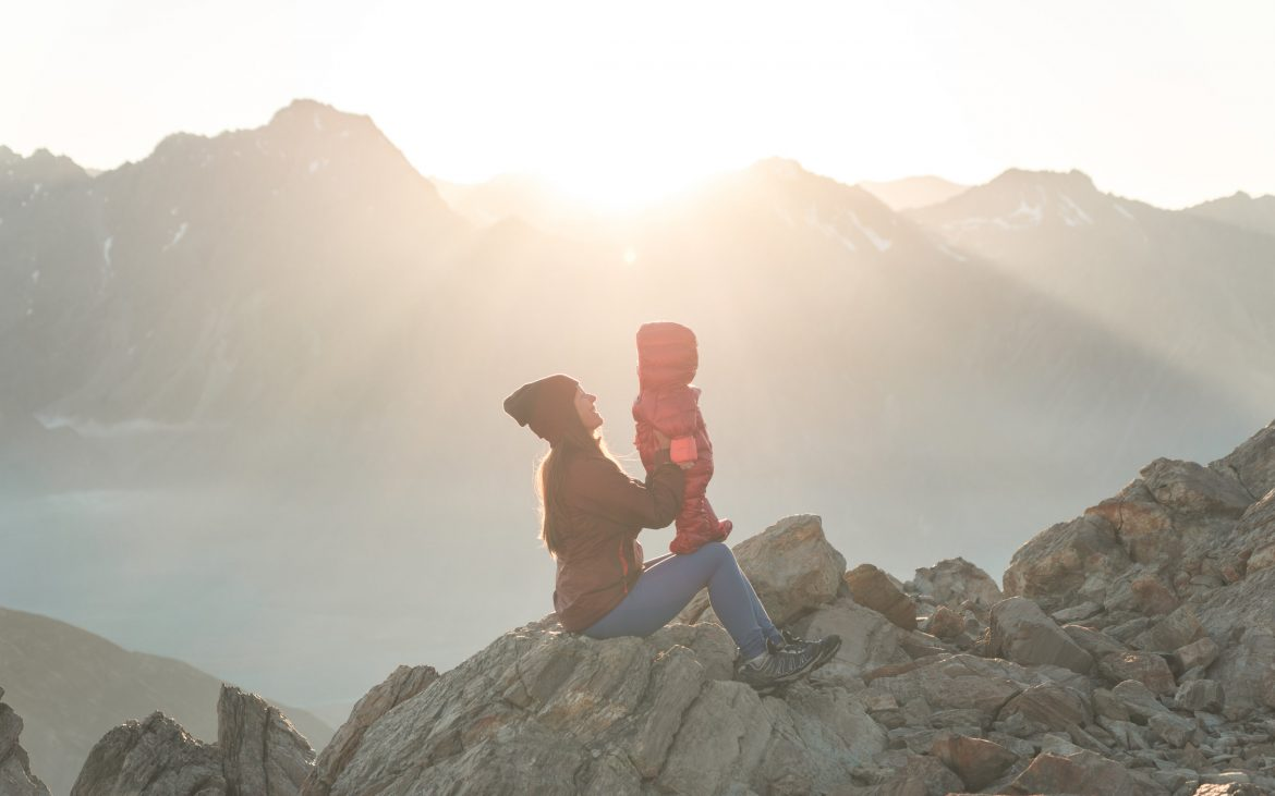 Mother holding daughter sitting on mountain top
