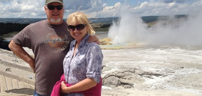 A couple in front of Old Faithful Geyser in Yellowstone.