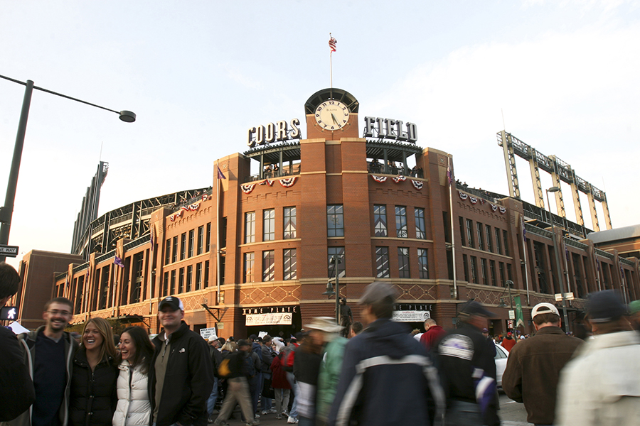 Baseball lovers gather outside the entrance of Coors Field, which sports a throwback exterior design.