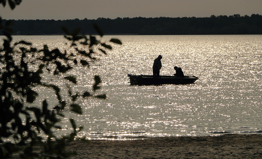 Silhouettes of a father and daughter on a lake at sunrise