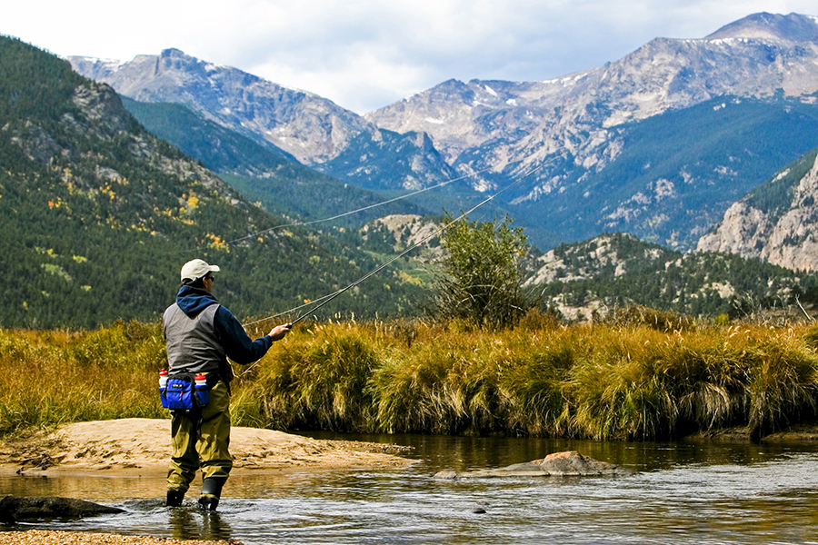 An angler casts a line in a stream in the Rocky Mountains.
