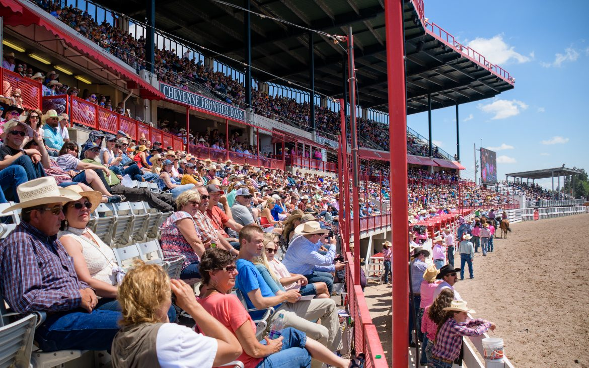 People in stands at rodeo on sunny day