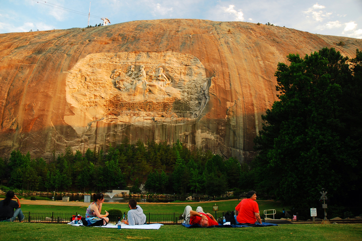 People have a picnic dinner under a large granite carving of Confederate Generals in Stone Mountain, Georgia