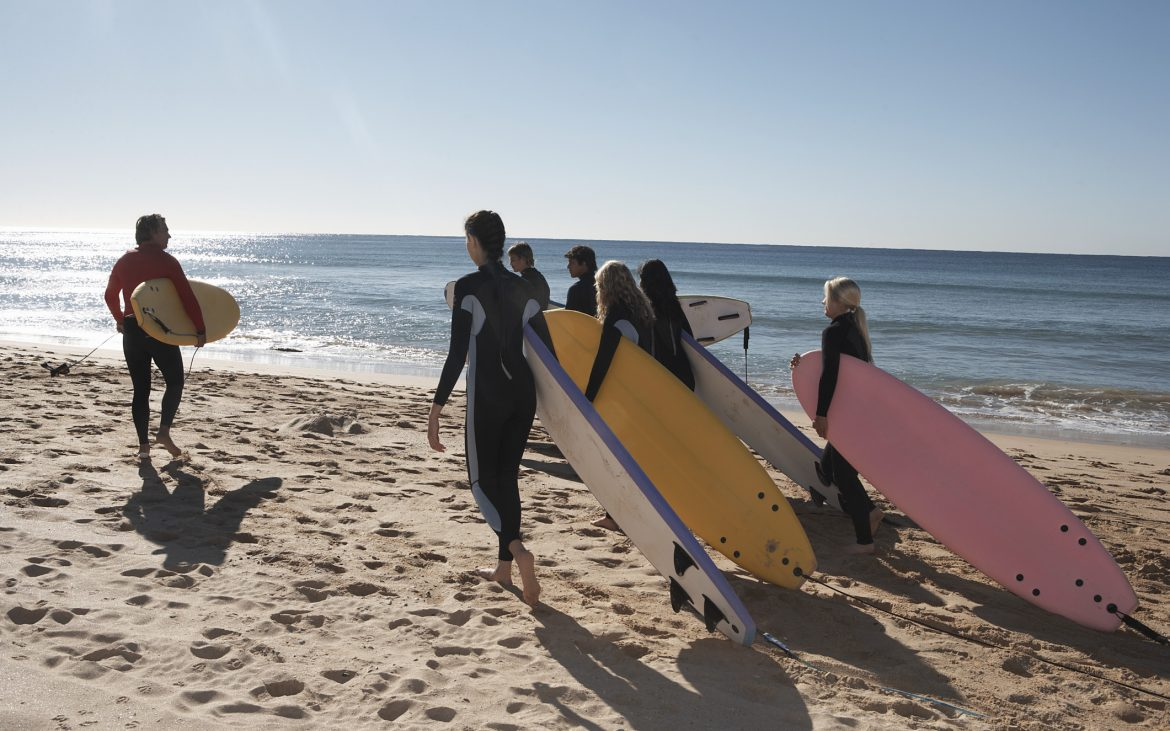 Group of surfers walking on the beach near water
