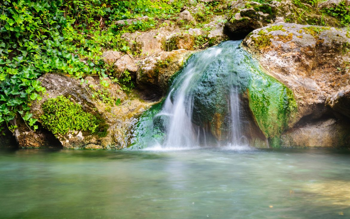Hot Springs waterfall into blue green water