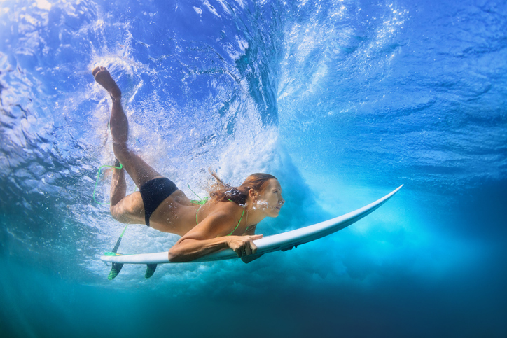 oung active girl in bikini in action - surfer with surf board dive underwater under breaking big ocean wave. Family lifestyle, people water sport adventure camp, beach extreme swim on summer vacation