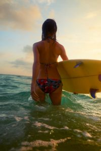 Young lady surfer walking into the sea with board
